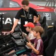 Stock Photo: Teenage boys drive simulators of racing game at Nismo G-Driv