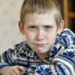 Foto Stock: 10-year-old boy with tears in eyes sits before textb