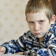 10-year-old boy with tears in eyes sits before textb — Stockfoto #39550455