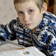 10-year-old boy with tears in eyes sits before textb — стоковое фото #39550463