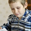 Stockfoto: 10-year-old boy sits with textbook, doing homework.