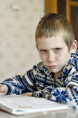The 10-year-old boy with tears in the eyes sits before the textb — Stock Photo