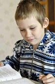 The 10-year-old boy sits with the textbook, doing homework. — Stock Photo