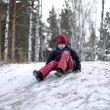 The teenage boy rides from a hill in the snow-covered wood. — Stock Photo #39856853