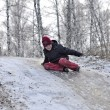 The teenage boy rides from a hill in the snow-covered wood. — Stock Photo #39856857