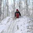 The teenage boy rides from a hill in the snow-covered wood. — Stock Photo
