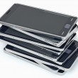 Heap of smart phones over white — Stock Photo