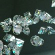 Large diamonds falling and rolling down over leather background - Foto Stock