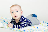 Cute baby in striped clothes lying down on a blanket — Stock Photo