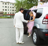 Wedding. The groom helps the bride out of the car — Stock Photo