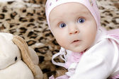 Surprised baby in a cap with a soft toy — Stock Photo