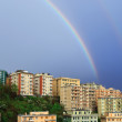 Rainbow over the town - Stock Photo
