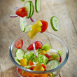 Fresh vegetables falling into the glass bowl — Stock Photo #49711581