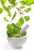 Green herbs falling into mortar and pestle — Stok fotoğraf