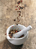 Various spices falling into mortar and pestle — Stock Photo