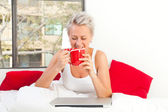 Portrait of a pretty woman sitting at her bed with a laptop and — Stock Photo