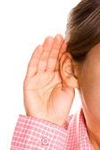 Girl listening with her hand on an ear — Stock Photo