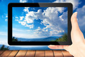 Ipad in hand for advertisement. with blue sky and clouds on monitor — Stock Photo