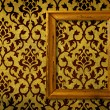 Gold frame on a vintage yellow wall background  — Stock Photo