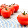 Fresh ripe tomatoes on an chopping board - Stock Photo