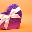 Stock Photo: Single heart gift box with ribbon on yellow background.