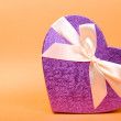 Single heart gift box with ribbon on yellow background. — Stock Photo