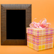 Wood photo frame and yellow gift box with pink ribbon on orange — Stock Photo