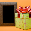 Wood photo frame and green gift box with red ribbon on orange ba — Stock Photo