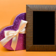 Stock Photo: Wood photo frame and heart gift box with ribbon on orange backgr