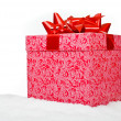 Stock Photo: Christmas red gift box with ribbon in snow on a white background