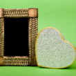 Stock Photo: Wood photo frame and heart gift box on green background.