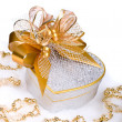 Foto Stock: Christmas silver heart gift box with golden ribbon in snow on a