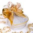 Christmas silver heart gift box with golden ribbon in snow on a - Stock Photo