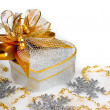 Photo: Christmas silver heart gift box with golden ribbon in snow on a