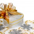 ストック写真: Christmas silver heart gift box with golden ribbon in snow on a