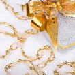 Foto de Stock  : Christmas silver heart gift box with golden ribbon in snow on a
