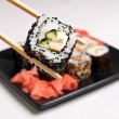Sushi on a black plate on white table. - Stock Photo