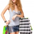 Young happy woman in dress with colorful shopping bags on a whit — Стоковая фотография