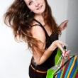 Young happy womin dress with colorful shopping bags on whit — Stock Photo #13490935