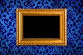 Gold frame on a vintage blue wall background — Foto de Stock