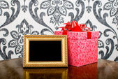 Golden photo frame and present box on table — Stock Photo