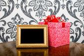 ゴールデン フォト フレームやテーブルの上にプレゼント ボックス — ストック写真