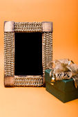Photo frame and gift box with ribbon on orange background. — Stock Photo