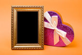 Gold photo frame and heart gift box with ribbon on orange backgr — Foto de Stock