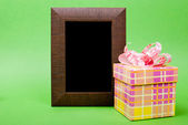 Wood photo frame and yellow gift box with pink ribbon on green b — Stock Photo