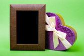 Wood photo frame and heart gift box with ribbon on green backgro — Stock Photo