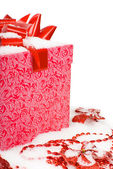 Christmas red gift box with ribbon in snow on a white background — Stock Photo