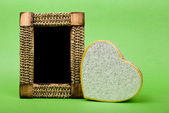 Wood photo frame and heart gift box on green background. — Stock Photo