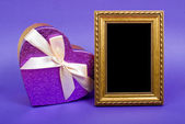 Gold photo frame and heart gift box with ribbon on blue backgrou — Zdjęcie stockowe