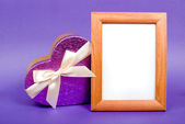 Wooden photo frame and heart gift box with ribbon on blue backgr — Stock Photo